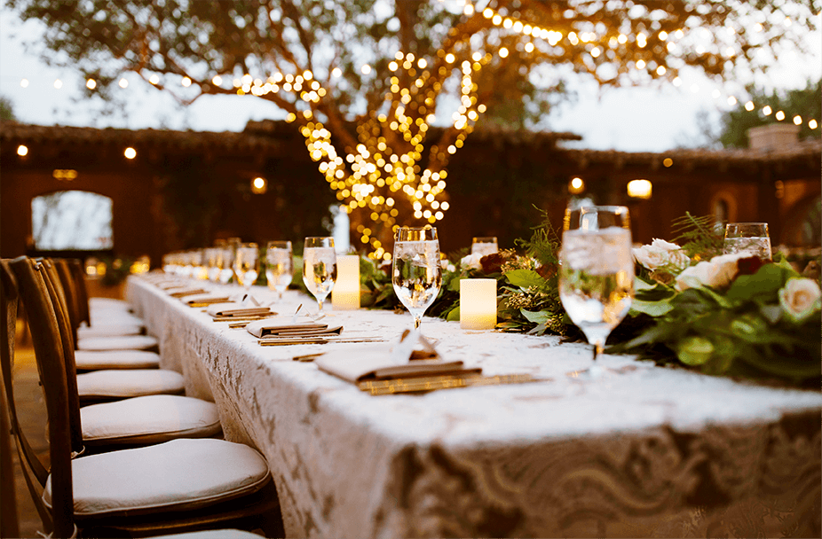 very long and elegant dining table set up outside at dusk with candles, fresh flowers, water glasses, place settings and invitation cards with tree covered in party lights in background