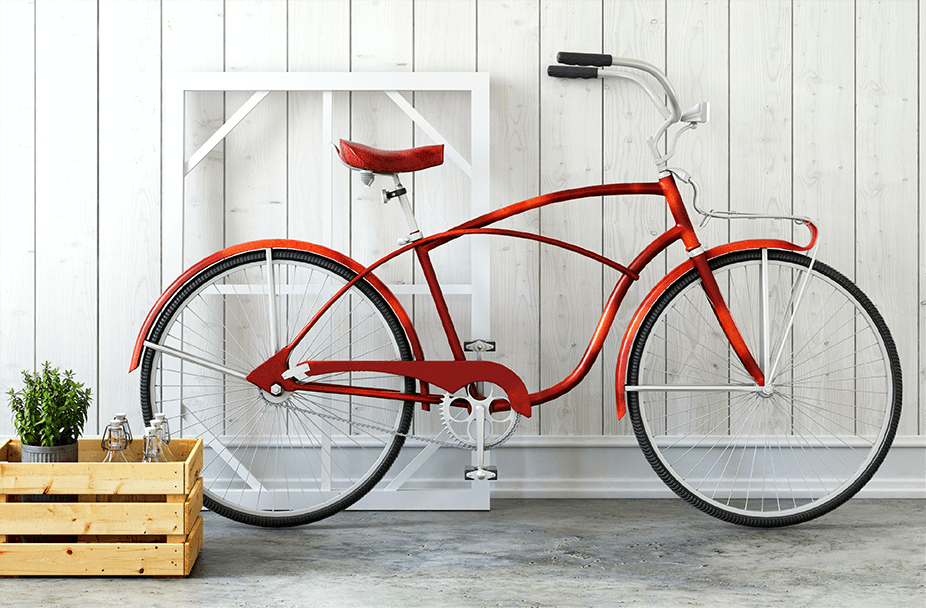 red cruiser-style vintage bicycle propped up again white wood wall and white window frame with wooden crate filled with fresh rosemary and glass bottles