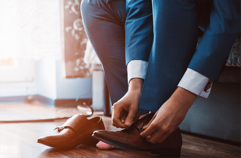 closeup of man in blue suit tying his brown leather shoes