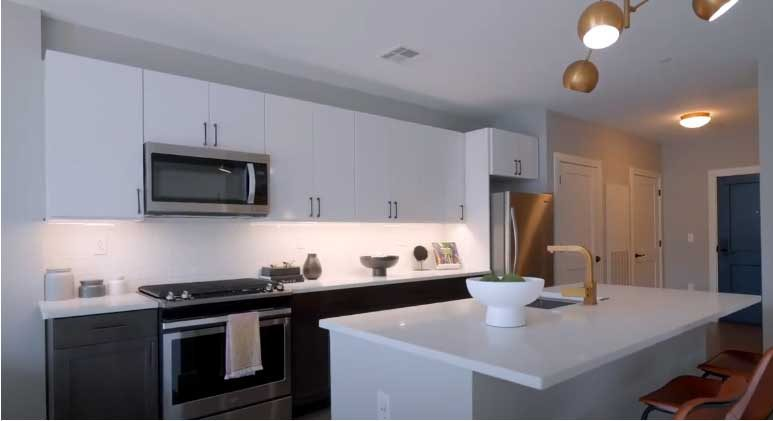 Kitchen with white cabinets, stainless steel appliances, and island with seating