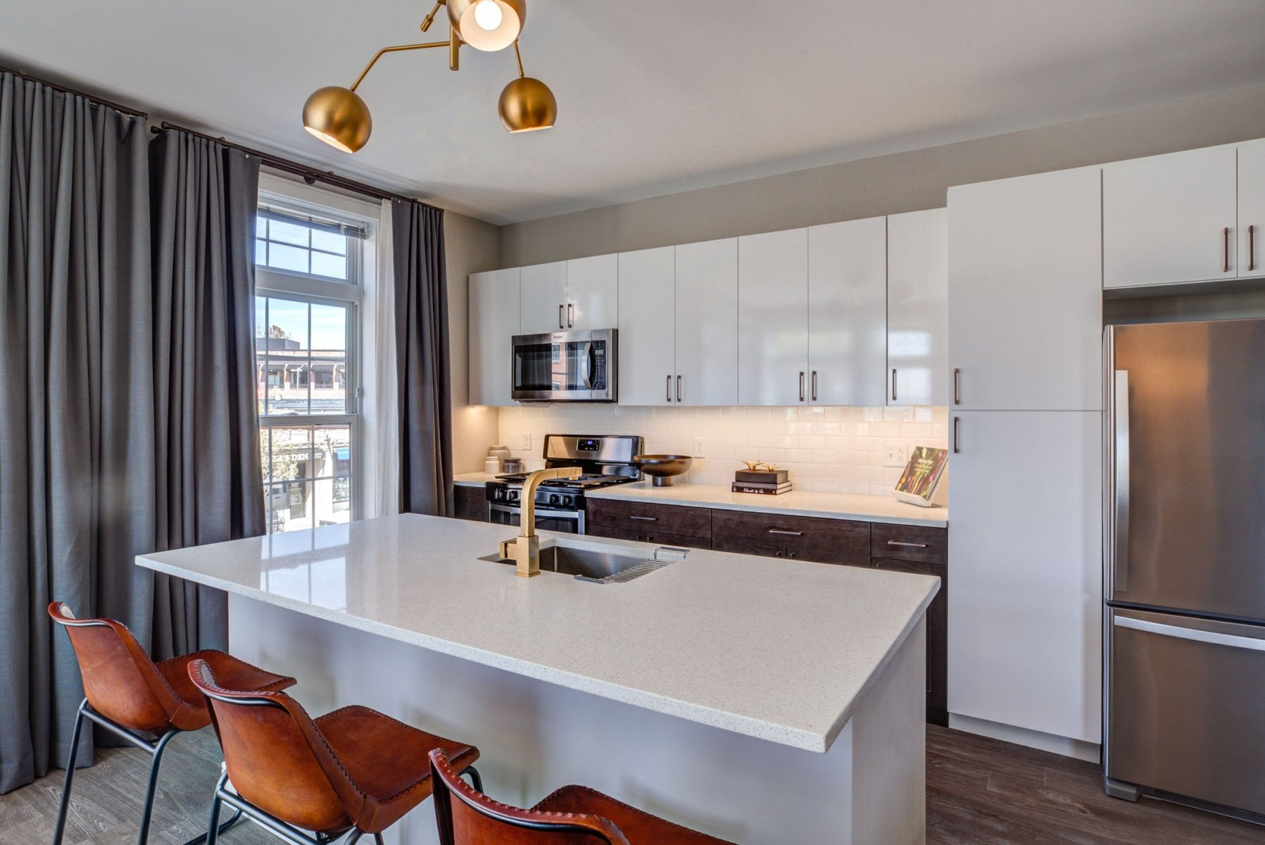 The Bradford apartment kitchen with two-tone cabinets, stainless steel appliances, quartz countertops, and large island with seating