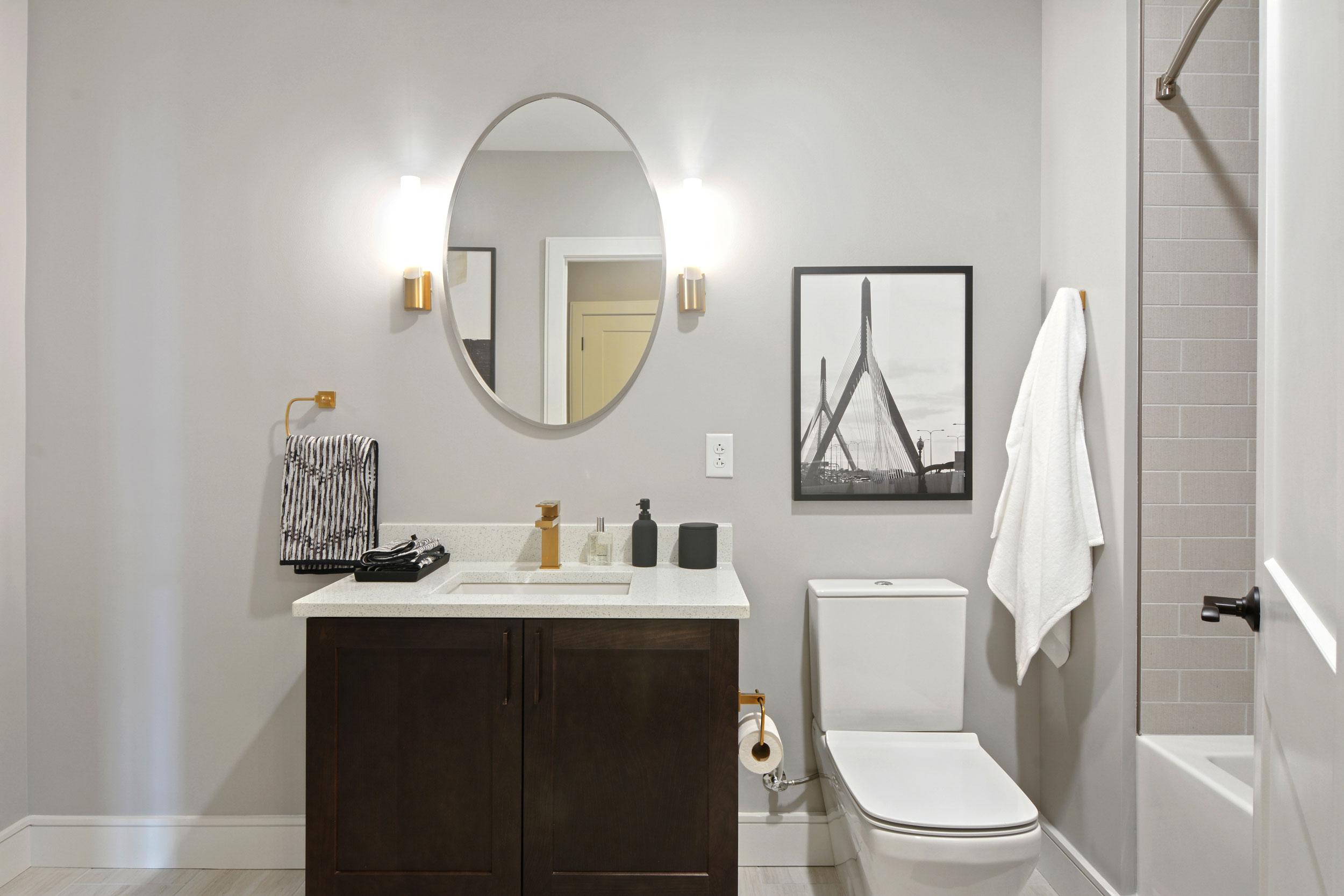 Restroom at The Bradford, featuring white quartz countertops, dark cabinets, round mirror