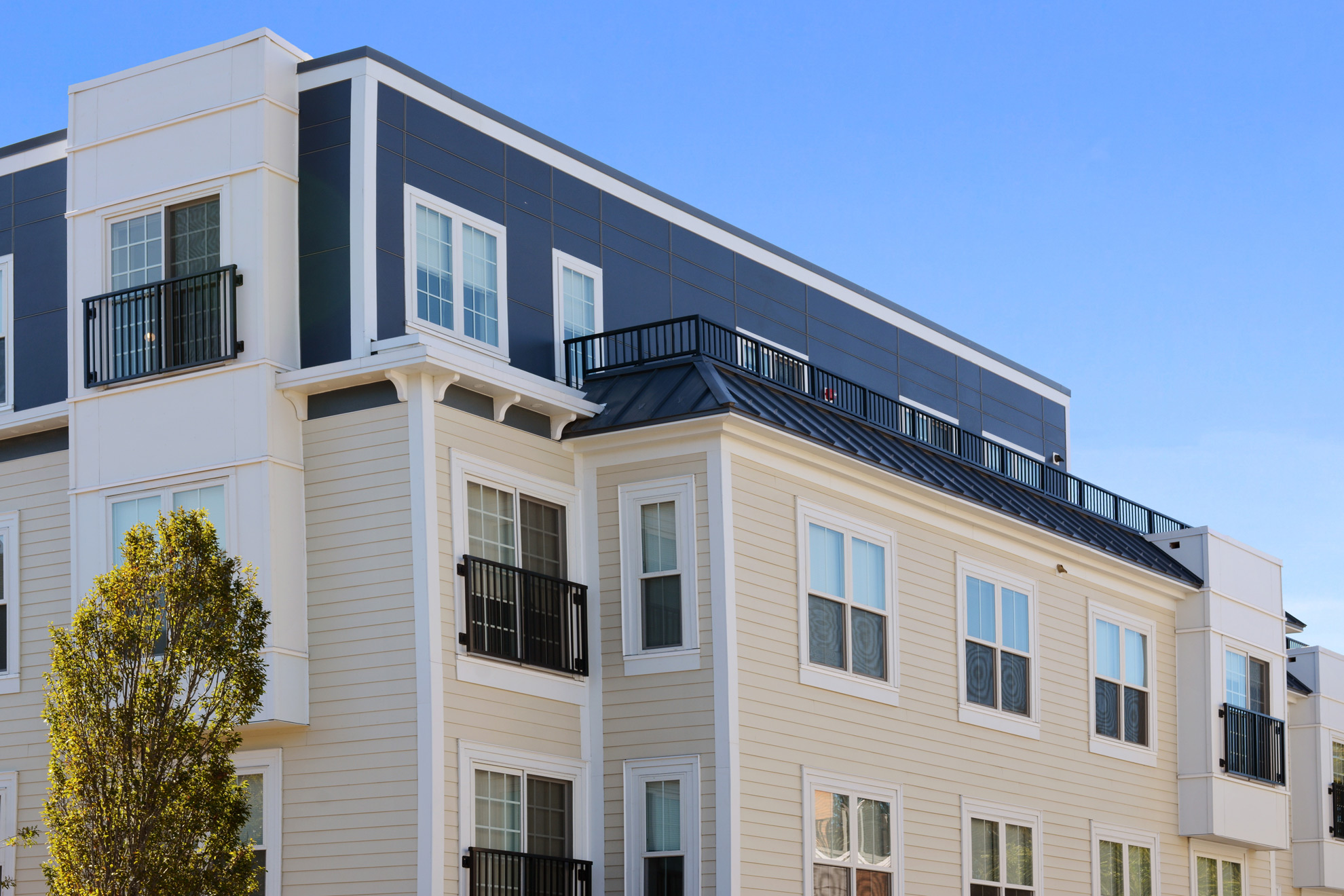 Closeup of the top of The Bradford at Belmont's large windows and rooftop deck